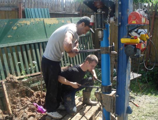 Рабочие монтируют обсадную трубу из пластика