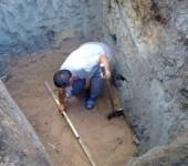 Рабочий в яме под септик
