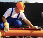 Строитель определяет угол уклона канализационной трубы