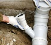белая канализационная труба и руки рабочего, который ее собирает
