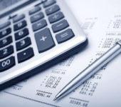 калькулятор и ручка на листе с формулами