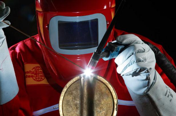 Сварщик варит детали из цветного металла